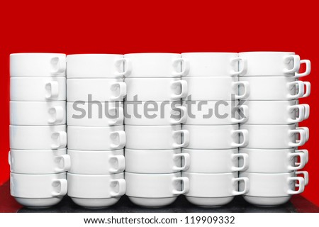 White cups for tea piled on table with plates for coffee-break with red background