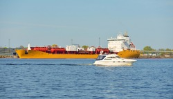 White cutter sailing in the Baltic sea. Tanker ship loading in port terminal in the background. Transportation, travel, cruise, sport, recreation, leisure activity, business, economy, industry, supply