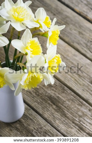 white daffodils at china vase on old weathered wood table