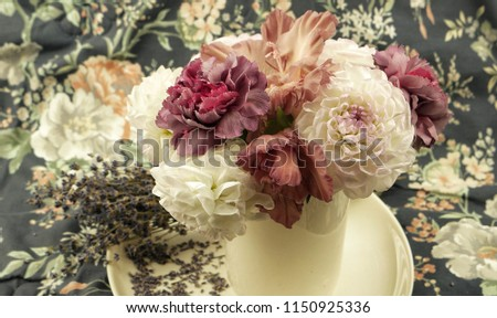 White dahlias and  pale pink carnations in a vase and a bouquet of dry lavender are on a white dish on a background of cloth with a floral pattern, floral composition. #1150925336