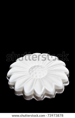 White daisy soap isolated on black, side view
