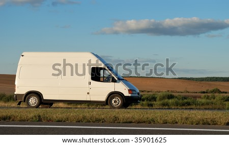 White delivery mini truck moving on the highway over blue sky. See my portfolio for trucks and lorries