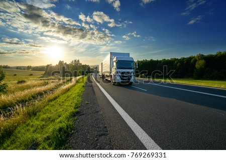 White delivery truck driving on the asphalt road in rural landscape at sunset #769269331
