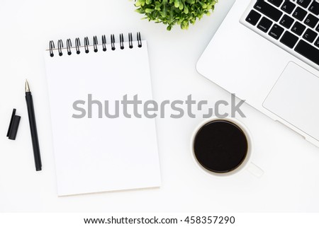 White designer office desk table with blank notebook page with pen, laptop computer and cup of coffee. Top view, flat lay.