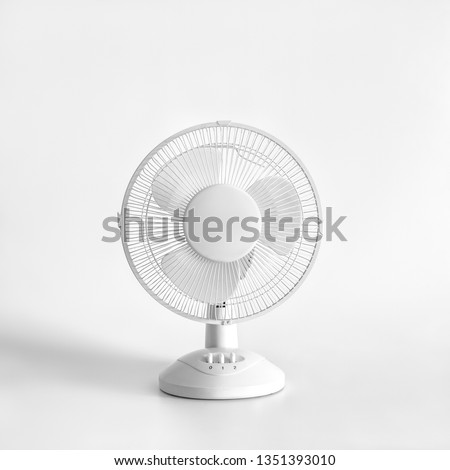 White desktop electric fan on light white background. Minimal concept. #1351393010