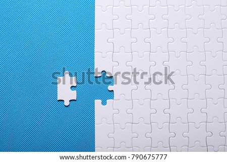 White details of a puzzle on blue background. A puzzle is a puzzle from small pieces. Heart shape of the details. Hands folding puzzle in white. #790675777