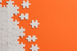 White details of puzzle on orange background.