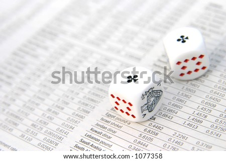 White dice on top of a financial newspaper.