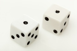 White dice with black dots against a white background