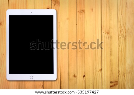 White digital tablet on bright wooden table