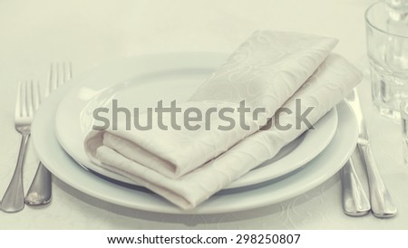 White dining table serving. White napkins, plates. forks, knifes