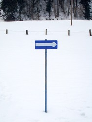 white direction arrow for oneway street on blue sign in snow