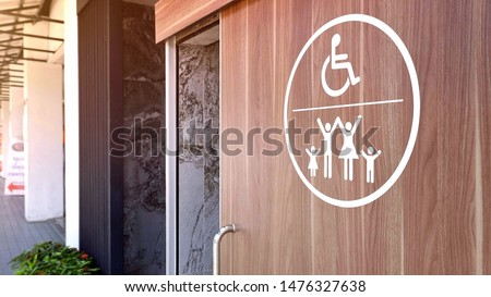 White disabled wheelchair and family restroom sign on wooden sliding bathroom door with blurred background in public area, selective focus #1476327638