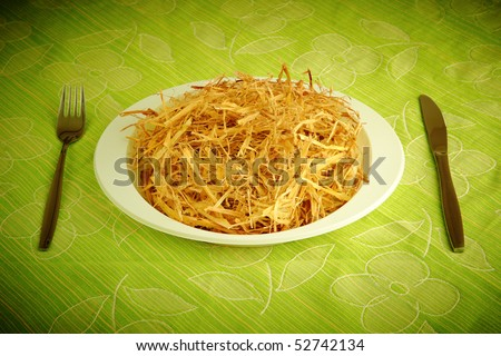 white dish full of straw with silverware on the table