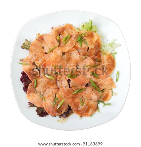 white dish with carpaccio of salmon on arugula over white background. Top view.