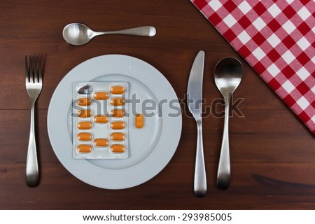 white dish with cutlery and pills on wooden table