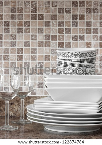 White dishes, plates and wineglasses on kitchen countertop.