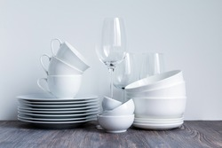 White dishware stacked on a wooden table against white background with transparent wineglasses