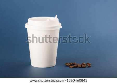 White disposable paper cup with white cap and coffee beans on a blue background