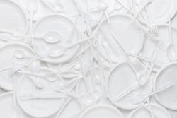 White disposable plastic tableware. Plastic plates, forks, spoons, knives. Abstract background of clean white dishes.