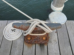 White docking line around a rusty cleat on a wooden pier.