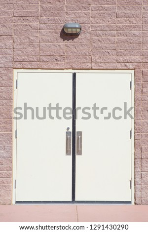 White door and chrome door handle with red brick wall of store room.