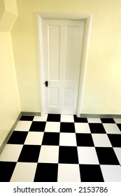 A stock photo of a white door and a black and white checkered floor. Slight distortion.