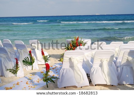 stock photo white draped chairs awaiting a Mexican beach wedding