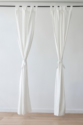 White drapery hanging from a curtain rod