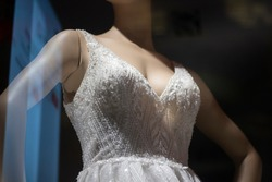 White dress on a mannequin. Lightweight fabric on a female mannequin to showcase outfits. Show of a wedding dress on a human figure.