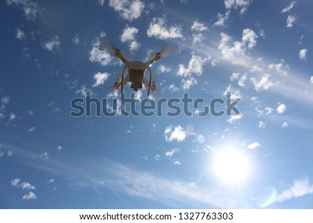 White drone fly in the blue sky and had beautiful white clouds. It was a very sunny daylight daytime. #1327763303
