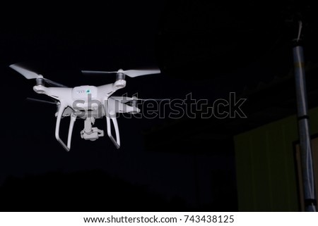 white drone flying at dark night. for take aerial photo.