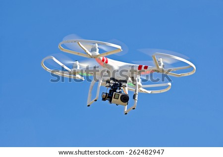 Shutterstock white drone hovering in a bright blue sky