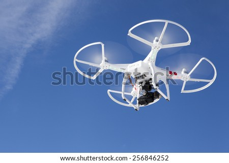 White drone in the sky.  Photo taken February 20th in Michigan.  Flying quadrocopter drone in the sky with mounted GoPro digital camera for video and photo productions.