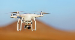 White drone quad copter with high resolution digital camera flying in the blue sky over the desert.