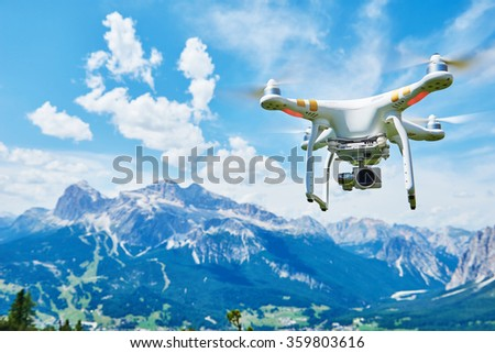 White drone quad copter with high resolution digital camera flying in the blue sky over the mountain