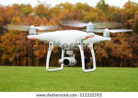 Shutterstock White drone quad copter with high resolution digital camera flying on autumn background.