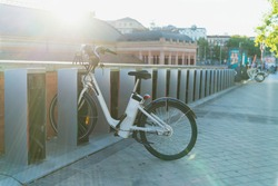White e-bike parked. it is in a bike parking during sunset. City landscape in background. Side view.