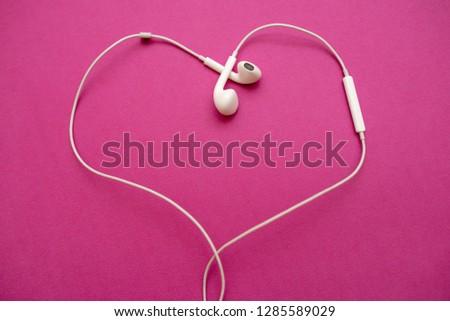 White earphone on pink background look like heart shape