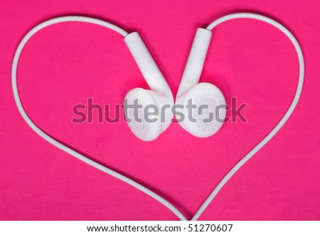 White earphone on pink background look like heart shape