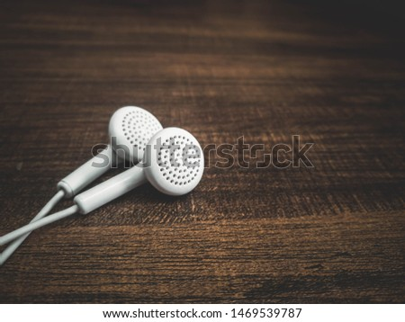 White earphone on wood texture background.
