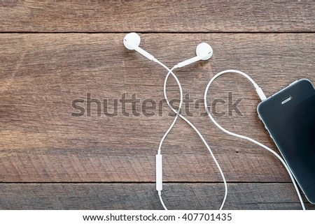white earphones and mobile phone on wooden background