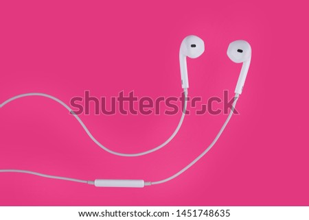 White earphones from the phone on pink background