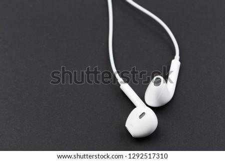 white earphones on black background