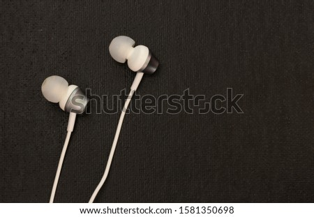 white earphones on black, traditional and affordable eletronics, high contrast and textured background with text space.