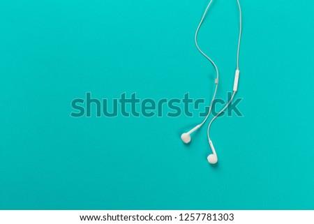 White earphones on menthol background