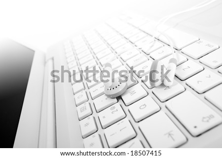 White earphones over a white keyboard suggesting mp3 online buy or download. Small DOF. Focus is on left earphone. - stock photo
