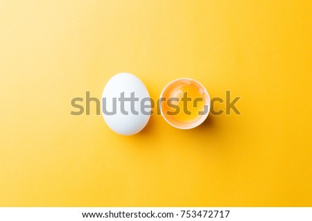 White egg and egg yolk on the yellow background.