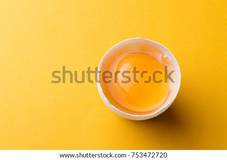 White egg and egg yolk on the yellow background. Сток-фото ©