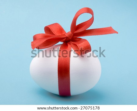 White egg wrapped around with red ribbon
